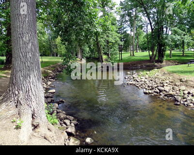 A peaceful stream under shady trees flowing through a park in rural Michigan. - Stock Photo