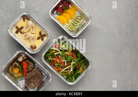 fast food in a foil box on a gray background. a healthy food close up. delivery from the restaurant a set of healthy - Stock Photo