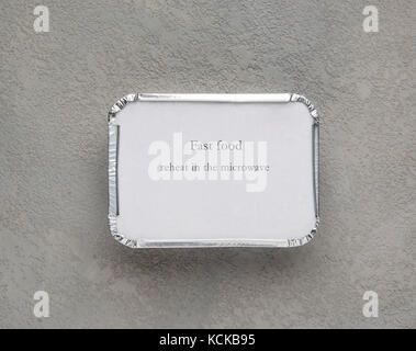fast food in a foil box on a gray rough background. food for businessman and busy people - Stock Photo