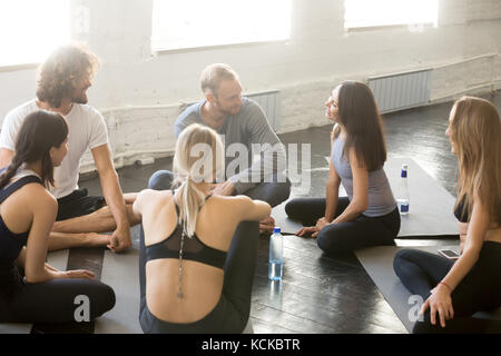 Group of sporty happy people sitting on the gym floor, students talking and resting after yoga class having an open - Stock Photo