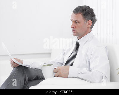 businessman reading a document while sitting in a chair in the hotel room. - Stock Photo