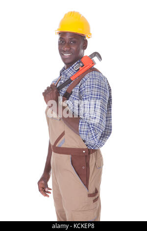 Young Happy Repairman Holding Wrench Over White Background - Stock Photo