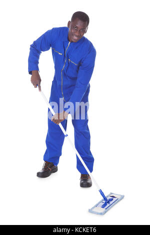 Young Man In Blue Suit Cleaning The Floor Over White Background - Stock Photo