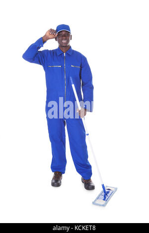 Young Man In Blue Boiler Suit Holding Mop Over White Background - Stock Photo