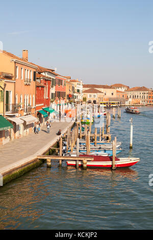 View along Riva Longa, Murano, Venice, Ialy at sunset with colorful buildings and moored boats, Few tourists walking - Stock Photo