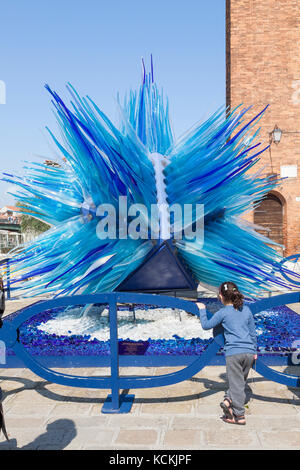 Little girl fascinated by the Comet Glass Star, Murano, Venice, Italy in Camp Santo Stefano desgigned by Simone - Stock Photo