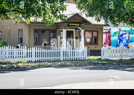 20's clapboard cottage with white picket fence, old shade trees serves as retail medical & recreational marijuana - Stock Photo