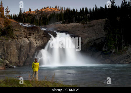 Hiker stands near the White Cascade waterfall along the Pacific Crest Trail in Yosemite National Park California - Stock Photo