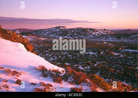 Mountain slope early on a spring morning, with snow. Ben Lomond National Park, Tasmania, Australia - Stock Photo