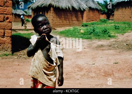 MANGUE, ANGOLA - May 15, 2007: A little boy stands with a torn shirt on a dusty road. - Stock Photo