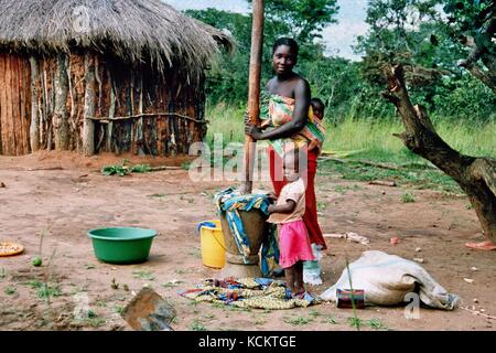 MANGUE, ANGOLA - May 15, 2007: A mother with her two children prepares Manjok to have something to eat. - Stock Photo