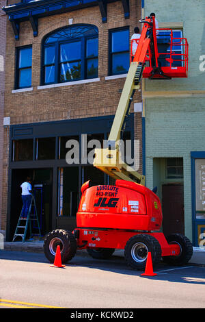 Men using a cherry picker to paint the exterior of a store in downtown Lebanon Tn, USA - Stock Photo