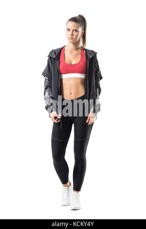 Beautiful fit active woman with perfect abs posing in sportswear with tracksuit jacket. Full body length portrait - Stock Photo