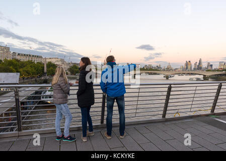 Tourists taking in the evening view down The Thames from Hungerford Bridge, London, England, UK - Stock Photo