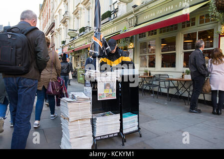 Newspaper vendor distributing free copies of the Evening Standard at a  street stand, London, England, UK - Stock Photo