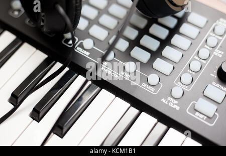 closeup photo of a mini keyboard with a pair of headphones - Stock Photo