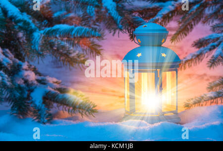 Christmas lantern with candle light and snow - Stock Photo