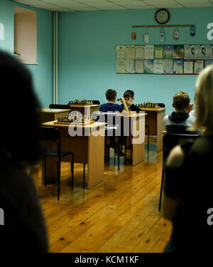 Two young kids sitting at a chessboard table play chess in an afterschool class in Russia - Stock Photo