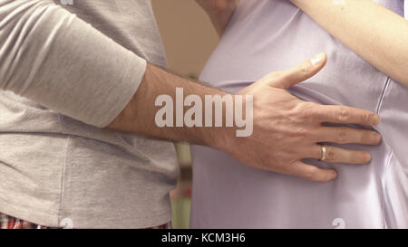 hands of husband on the tummy of his pregnant wife. husband tenderly stroked pregnant belly of his wife. Young man - Stock Photo