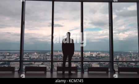 Rear view of businessman in an office with panoramic city view. Businessman admires the city from the panoramic - Stock Photo