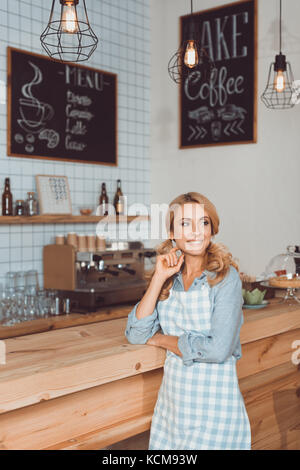 beautiful cafe owner in apron - Stock Photo