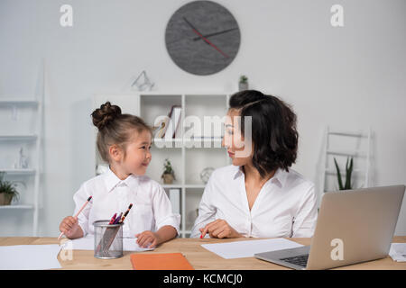 asian businesswoman with daughter in office - Stock Photo