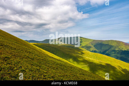 gorgeous green rolling hill in summer. beautiful view of grassy mountain slopes under cloudy sky - Stock Photo