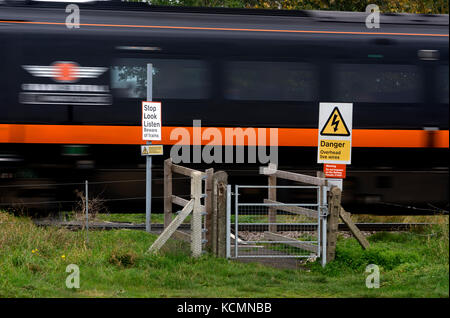 Grand Central train at speed passing a foot crossing on the East Coast Main Line, Nottinghamshire, England, UK - Stock Photo