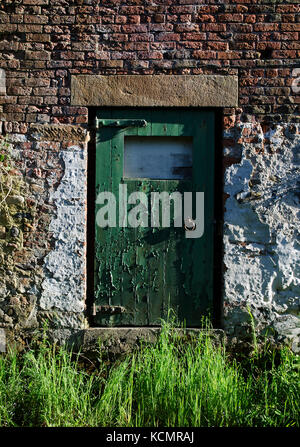 Old green wooden door with peeling paint in an old barn in Lancashire, UK - Stock Photo