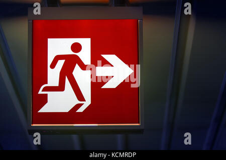 The emergency exit sign shows the direction of escape in case of danger. The emergency exit board hangs on the ceiling - Stock Photo