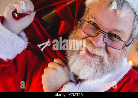 Portrait of santa claus carrying his gift sack - Stock Photo
