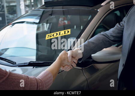 Cropped image of salesman doing handshake with customer while standing by car in showroom - Stock Photo