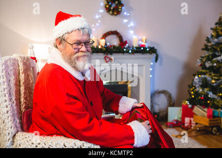 Santa Claus putting presents in christmas bag at home - Stock Photo