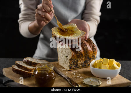 Close-up of woman applying jam over multigrain bread slice - Stock Photo