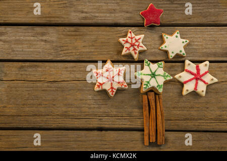 Overhead view of Christmas tree made with star shape cookies and cinnamon sticks on wooden table - Stock Photo