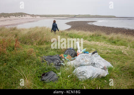 A walker passes a pile of assorted plastic materials awaiting removal from the coastal landscape, having been collected - Stock Photo