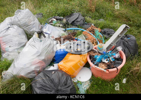 A pile of assorted plastic materials await removal from the coastal landscape, having been collected by volunteers - Stock Photo