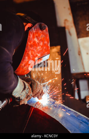 worker welding metal with sparks and smoke in the helmet - Stock Photo
