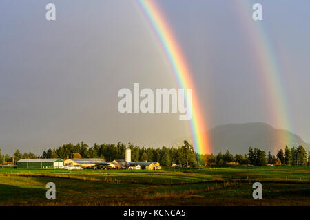 A double rainbow over a farm in Cowichan Bay, British Columbia. - Stock Photo