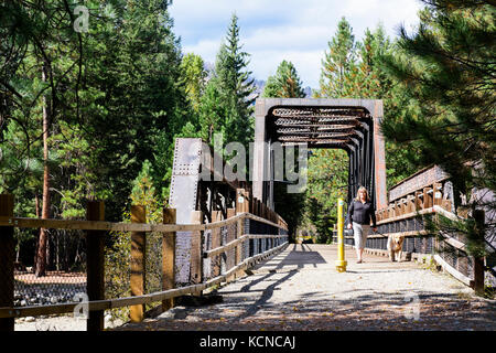 A woman and her Golden Retriever (Canis lupus familiaris) walking across a trestle (part of the Kettle Valley Railway) - Stock Photo