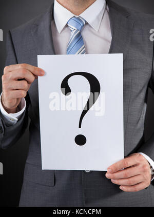 Close-up Of Businessperson Holding Board With A Question Mark - Stock Photo