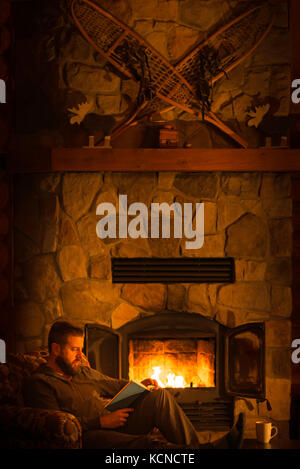 Man (40) sitting by a warm open fire at a log cabin ski chalet in Mont Tremblant, Quebec, Canada - Stock Photo