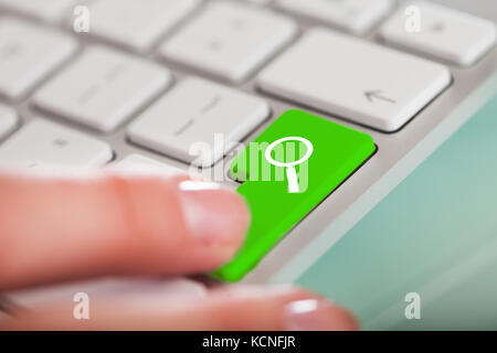 Close-up Of Hand Over Search Enter Button On Keyboard - Stock Photo