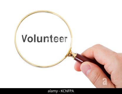 Close-up Of Hand Showing Volunteer Word Through Magnifying Glass Over White Background - Stock Photo