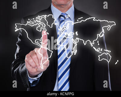 Businessman touching world map on the screen over black background - Stock Photo