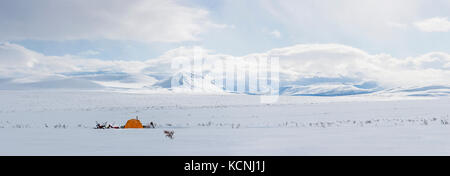 Snowmobilers camp under the McKenzie Mountains overlooking a high tundra plateau in the middle of winter's grip - Stock Photo