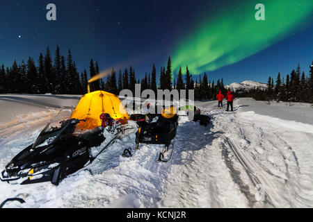 Snowmobilers camped for the night are greeted with Northern lights while traveling along the North Canol Heritage - Stock Photo