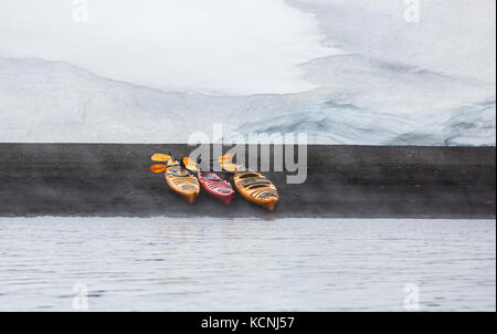 Three Kayaks lined up on the volcanic beach of Whalers Bay become the centre of interest in a simple design, Deception - Stock Photo