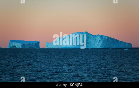 Twilight finds Icebergs floating in water against an orange cloudless sky near Fournier Bay, Antarctic Peninsula - Stock Photo