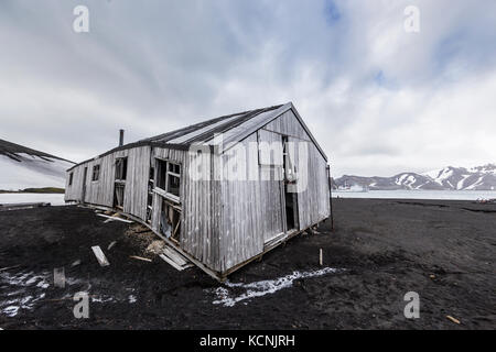 Long abandoned buildings slowly deteriate in the harsh and bleak environment at Deception Island, South Shetland - Stock Photo
